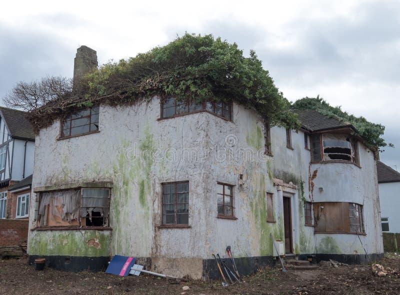Yttersida av det övergivna huset som byggs i 30-taldecostil, harv UK arkivfoton