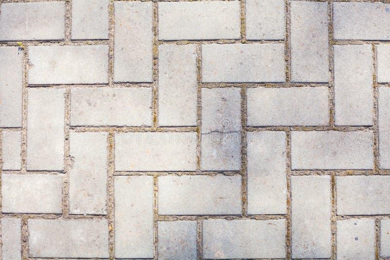 Yttersida av det gamla packade golvet med tegelstenar eller blöjan för vit geometrisk arkitektur symmetriska upprepade modelllodl royaltyfria bilder