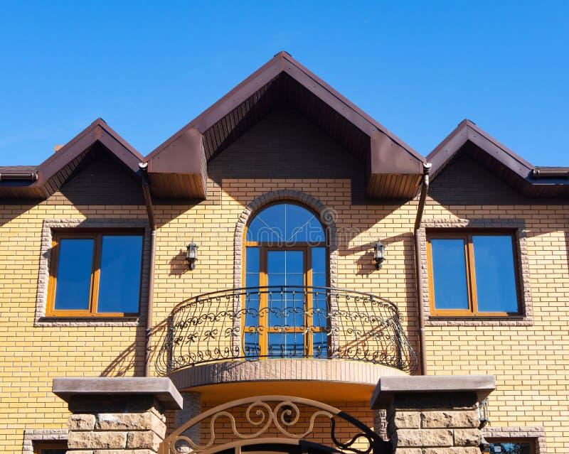 Yttersida av det moderna tegelstenhuset med förfalskningbalkongen, fönster och stuprännor arkivbild
