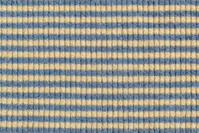 Yttersida av det stack tyget av naturlig ull med närbild för gula och blåa band Textur för varm vinterkläder royaltyfria foton