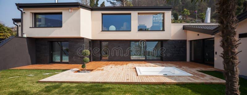 Yttersida av en modern villa, veranda med badkaret royaltyfria foton