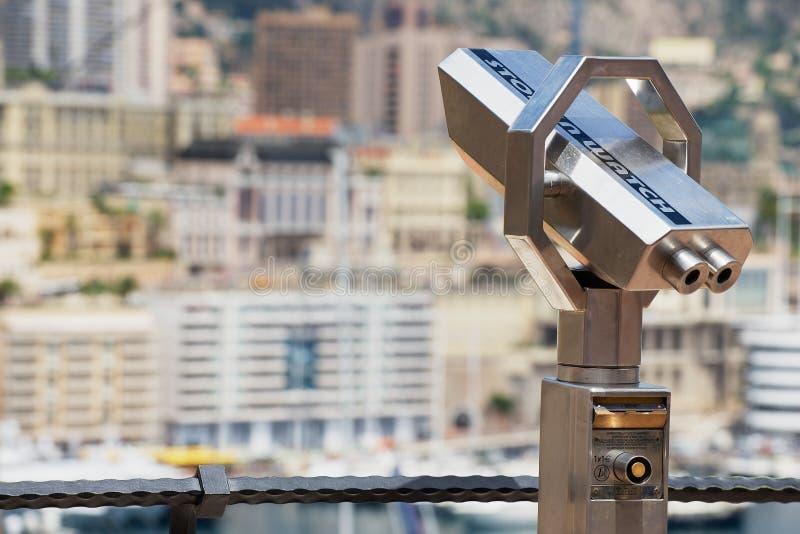 Yttersida av myntet fungerade binokulärt på synvinkeln med den stads- panoraman på bakgrunden i Monaco arkivbild