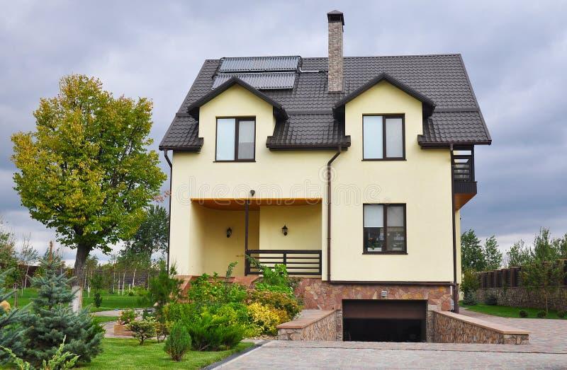 Yttersida för begrepp för byggnad för hus för energieffektivitet ny passiv Hemtrevligt hus med sol- vattenpaneluppvärmning, takfö fotografering för bildbyråer