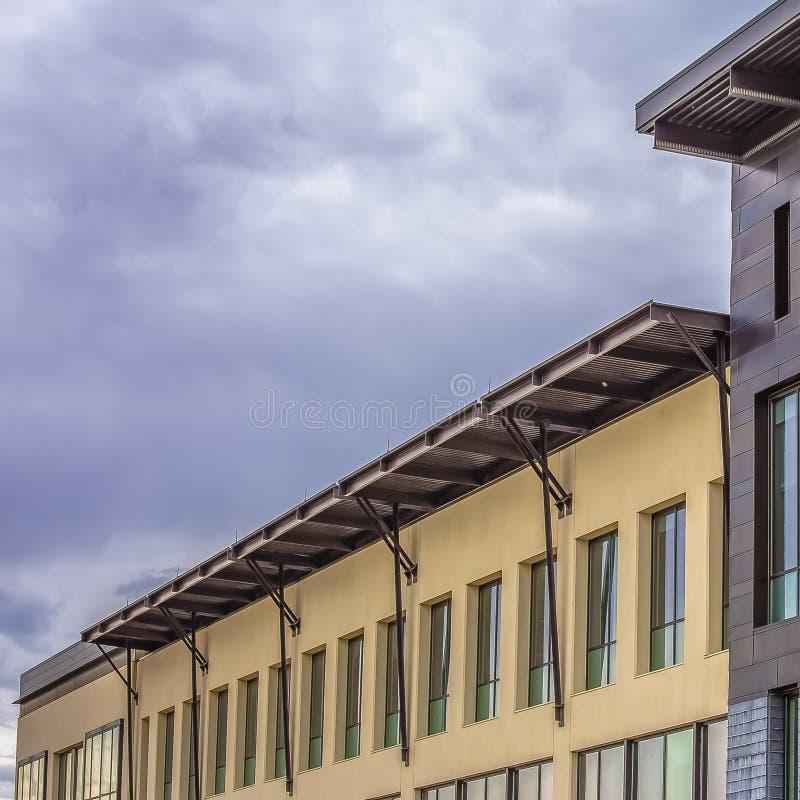 Yttersida för fyrkantbyggnad med ett plant tak mot himmel som täckas med pösiga gråa moln royaltyfria foton