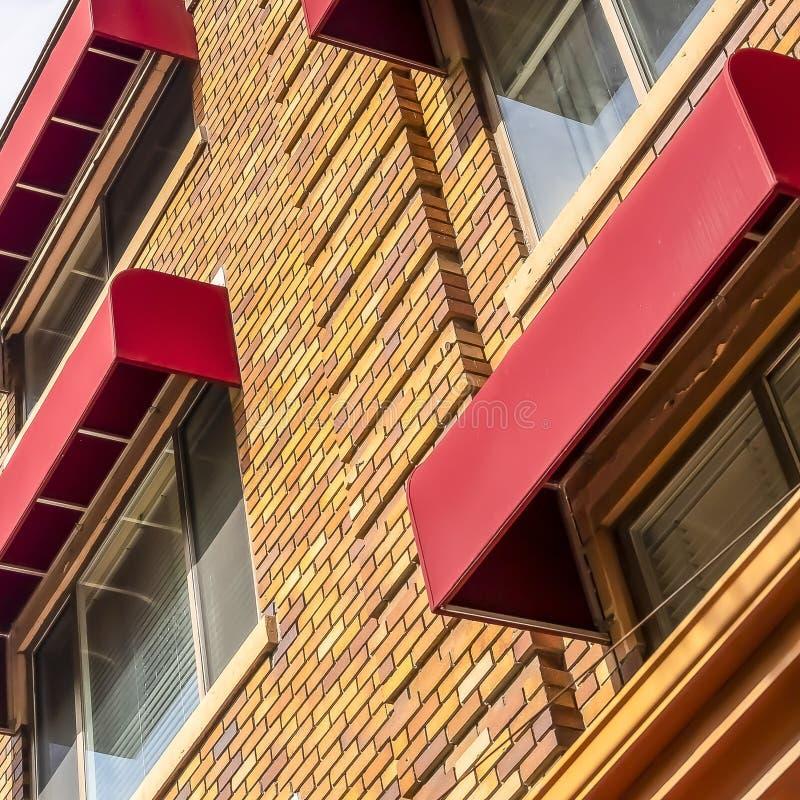 Yttersida för fyrkantrambyggnad som presenterar stentegelstenväggen och röda markiser på fönstren arkivbilder