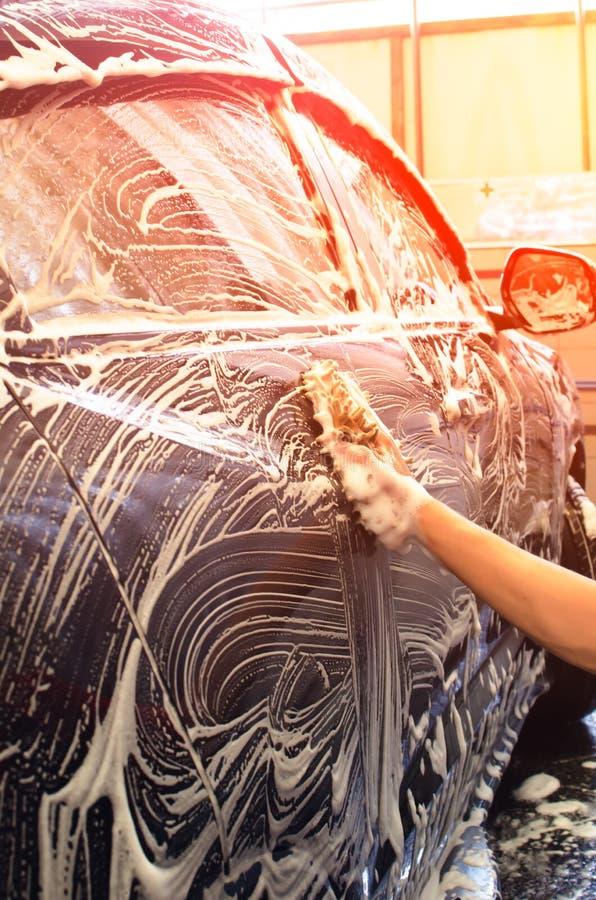 Yttersida för handtvagningbil med bubblaskum och mikrofibertorkduken royaltyfri fotografi