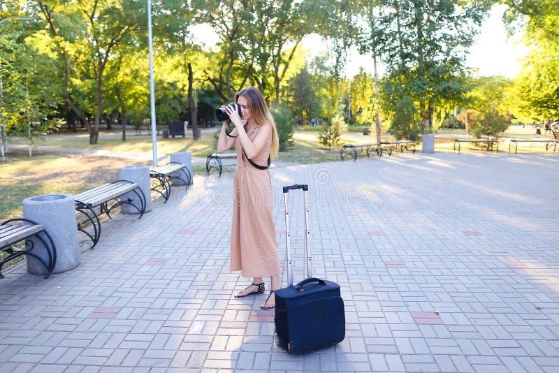 Yttersida för klänning för ung reporter bärande stående med kameran och valise royaltyfri fotografi