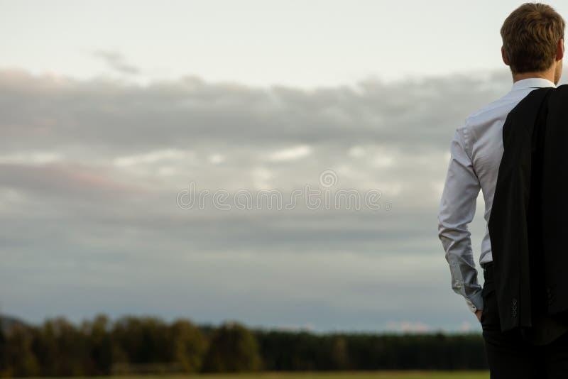 Yttersida för Yong affärsmananseende i naturen som ser in i avståndet arkivfoto