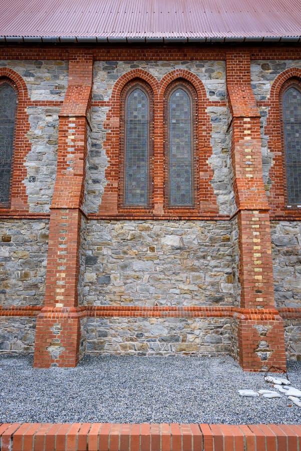 Yttre detalj för sten och för tegelsten av Kristuskyrkadomkyrkan, fläckexponeringsglasfönster, rött metalltak, grusgård royaltyfri bild