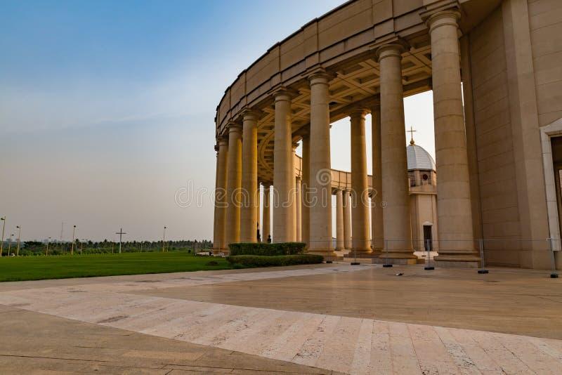 Yttre sikt av en av kolonnaderna av basilikan av vår dam av fred med inställningssolen till det västra royaltyfria bilder