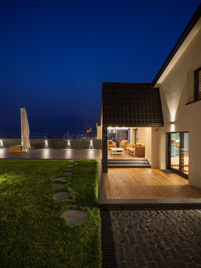 Yttre sikt av en modern lyxig villa, nattlig plats royaltyfri foto
