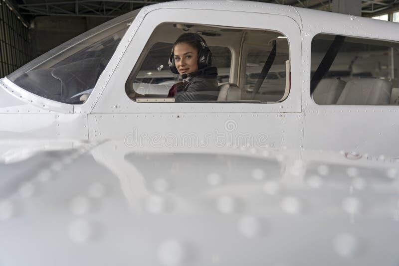 Yttre sikt av flygplan och den härliga kvinnapiloten With Headset i cockpiten arkivbild