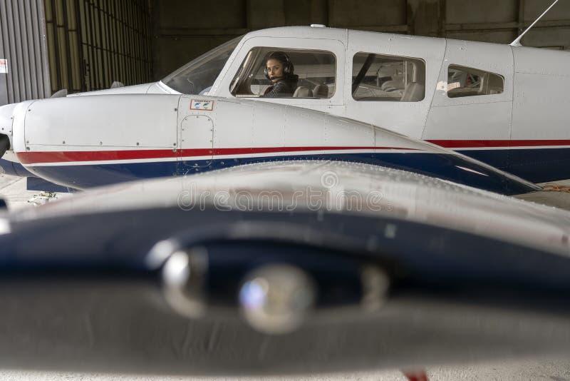 Yttre sikt av flygplan- och kvinnapiloten With Headset i cockpiten arkivfoto