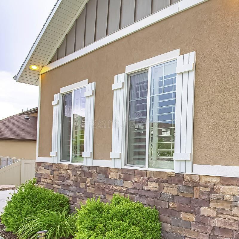 Yttre sikt för fyrkantig ram av hemmet med den stenlade banan som leder till ytterdörren med sidomarkeringsljuset arkivbilder