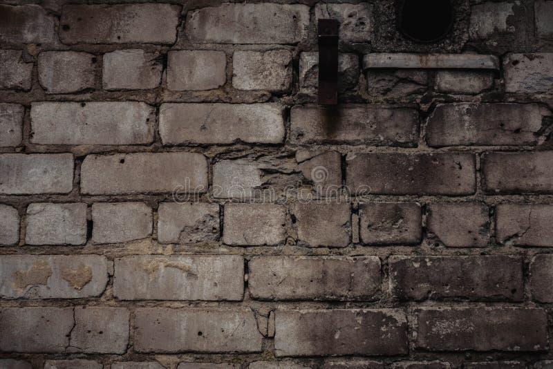 Yttre tegelstenvägg med nedfläckad och skalande vit målarfärg och den brända väggen royaltyfri bild