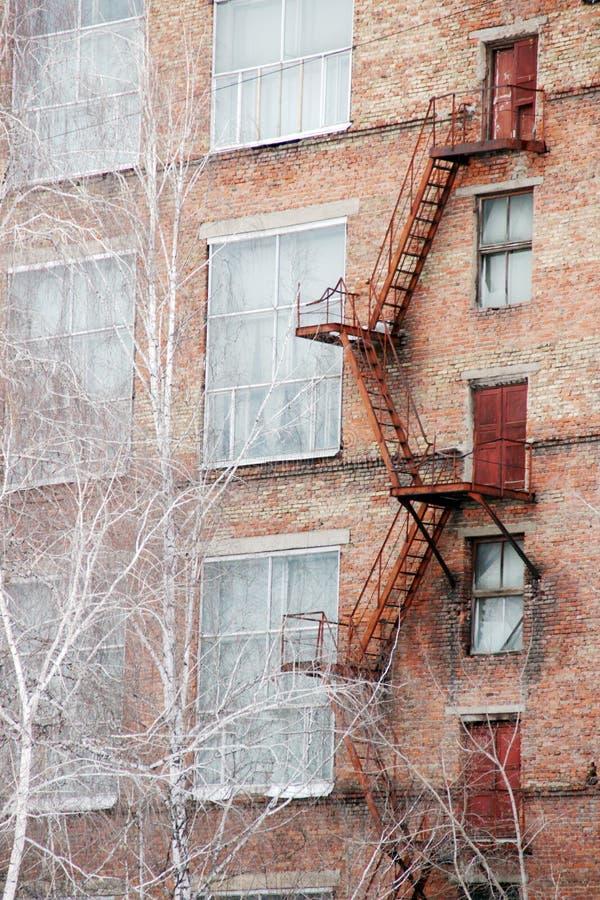Yttre trappuppgång för brandflykt på en gammal tegelstenbyggnad av fabriken, växt Stora fönster, träd för den vita björken växer  royaltyfri fotografi