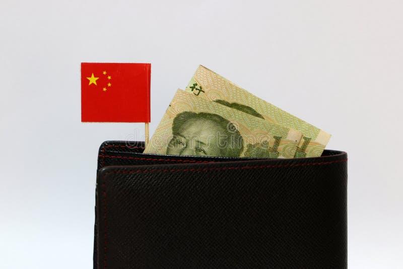 Yuan sedel av Kina och den mini- flaggapinnen för kinesisk nation på den svarta plånboken med vit bakgrund fotografering för bildbyråer