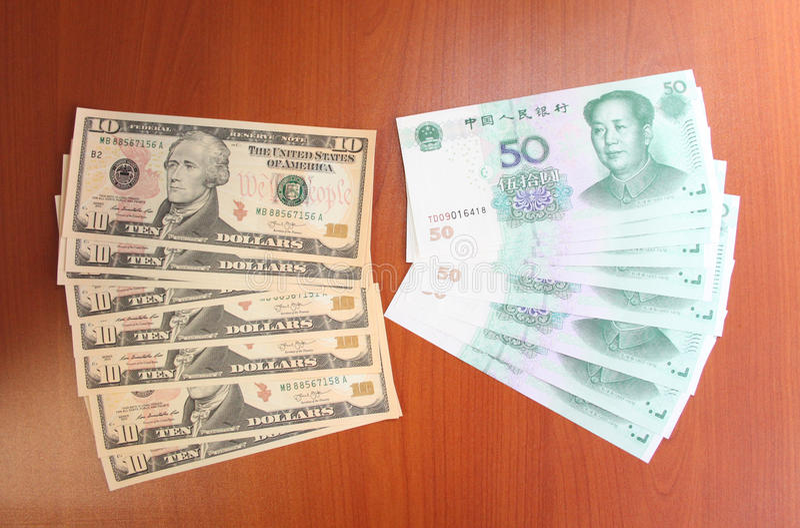Yuans chineses por cinqüênta (50), dólares de Estados Unidos (10) pela denominação dez estão em uma tabela antes de uma viagem a  imagem de stock