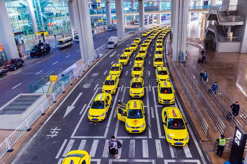 Group of yellow taxi cabs waiting arrival passengers in front of Airport Gate. Chongqing Jiangbei international airport in CHINA royalty free stock photo