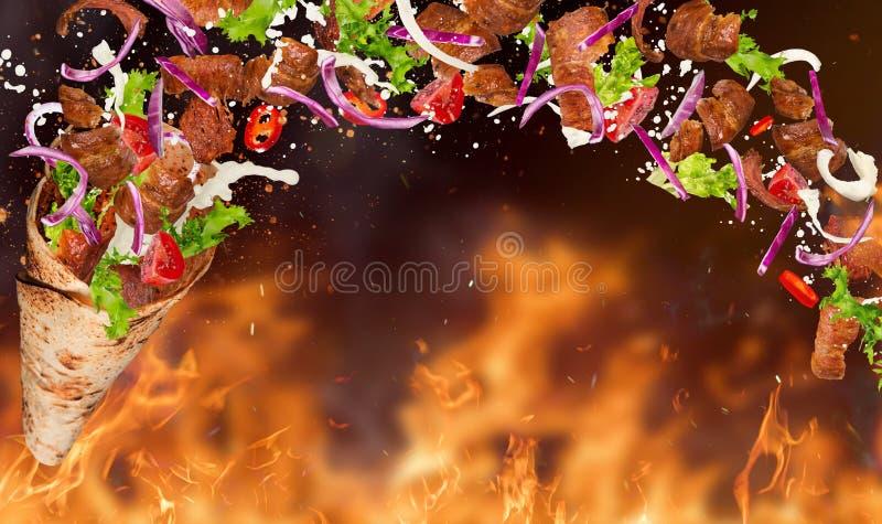 Yufka turco del kebab con los ingredientes y las llamas del vuelo imagen de archivo libre de regalías