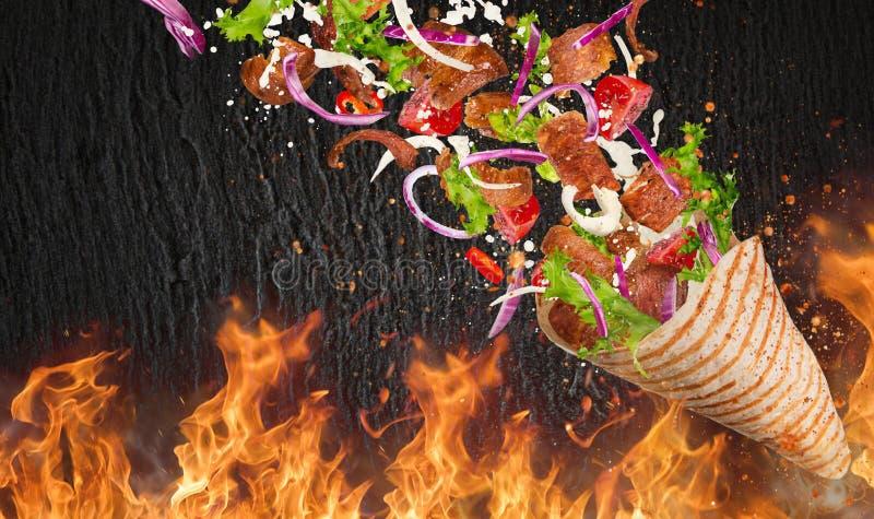 Yufka turco del kebab con los ingredientes y las llamas del vuelo imagen de archivo