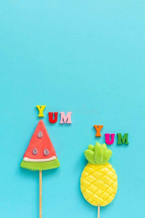 Yum κείμενο, ανανάς και καρπούζι Yum ζωηρόχρωμο lollipops στο ραβδί στο μπλε κίτρινο υπόβαθρο Διακοπές έννοιας ή στοκ εικόνες