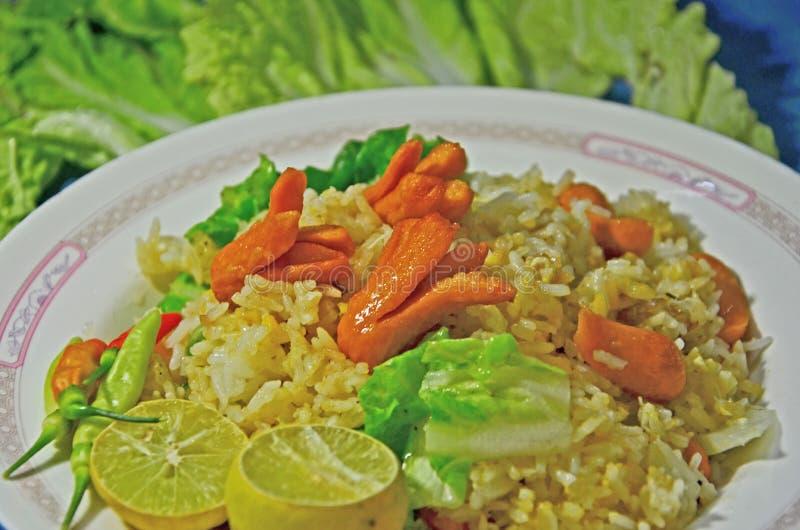 Yummy τηγανισμένο ρύζι με το χοτ ντογκ και το φυτικό πιάτο στοκ εικόνα