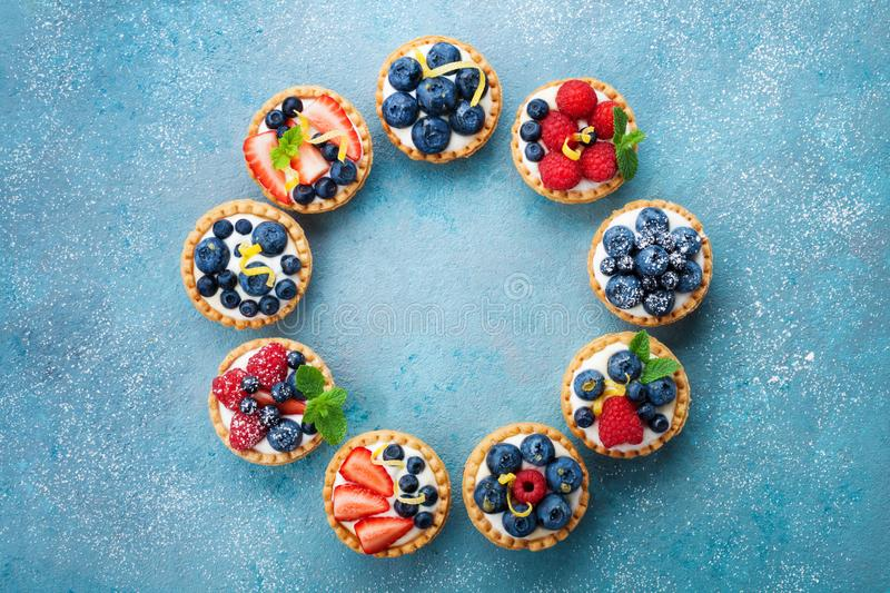Yummy berry tartlets or cake with cream cheese. Summer pastry dessert on turquoise table from above. royalty free stock photos
