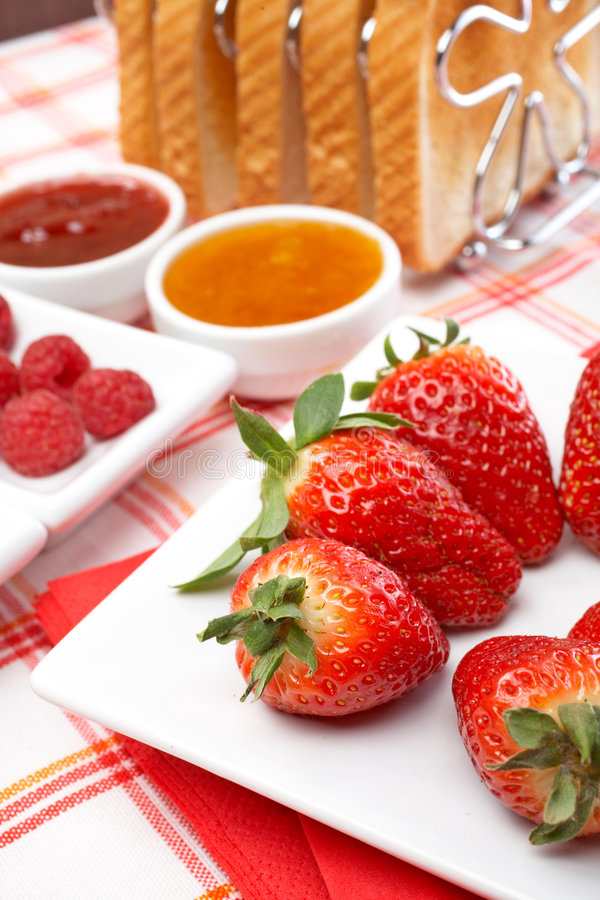 Yummy breakfast. Strawberries, raspberries, slices of bread and jam for healthy breakfast. Shallow DOF royalty free stock photos