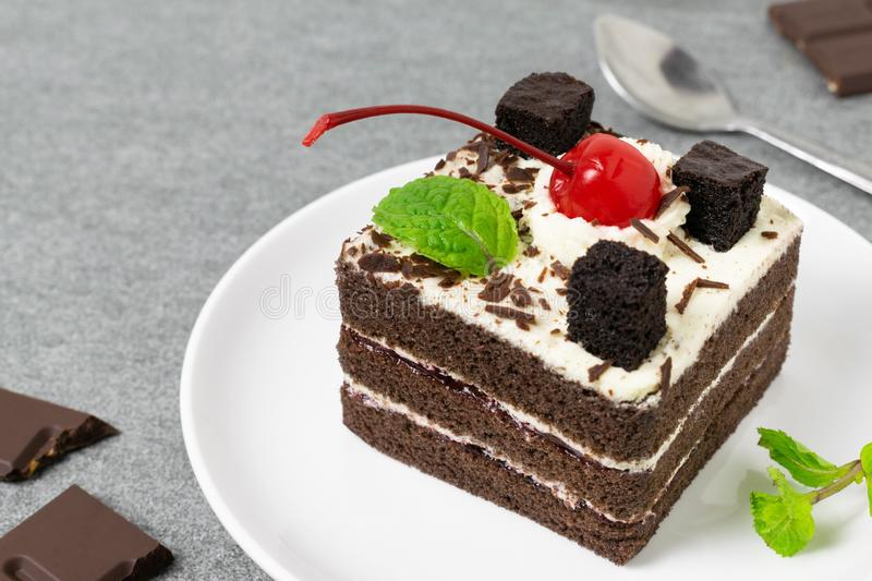 Yummy chocolate cake with cherry and mint leaves in white dish on tile table royalty free stock images