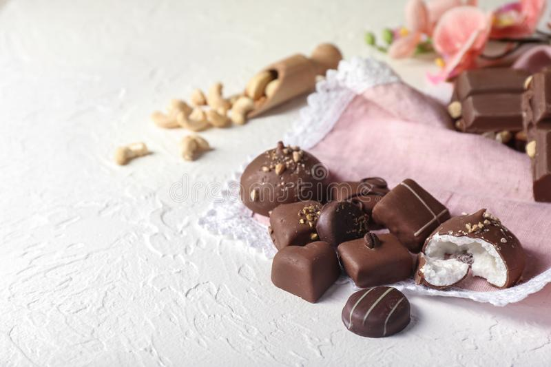 Yummy chocolate candies on white textured background stock images