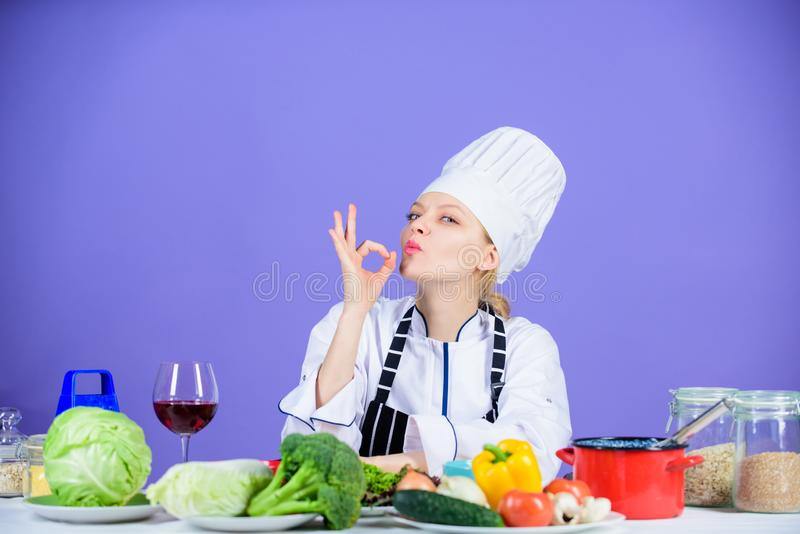 Yummy cooking. Kitchen maid showing OK gesture. Pretty woman cooking in restaurant kitchen. Professional cook confident royalty free stock photography