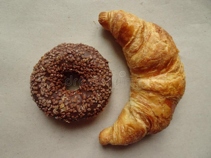 Yummy croissant and chocolate donut on rough paper. Top view royalty free stock photos