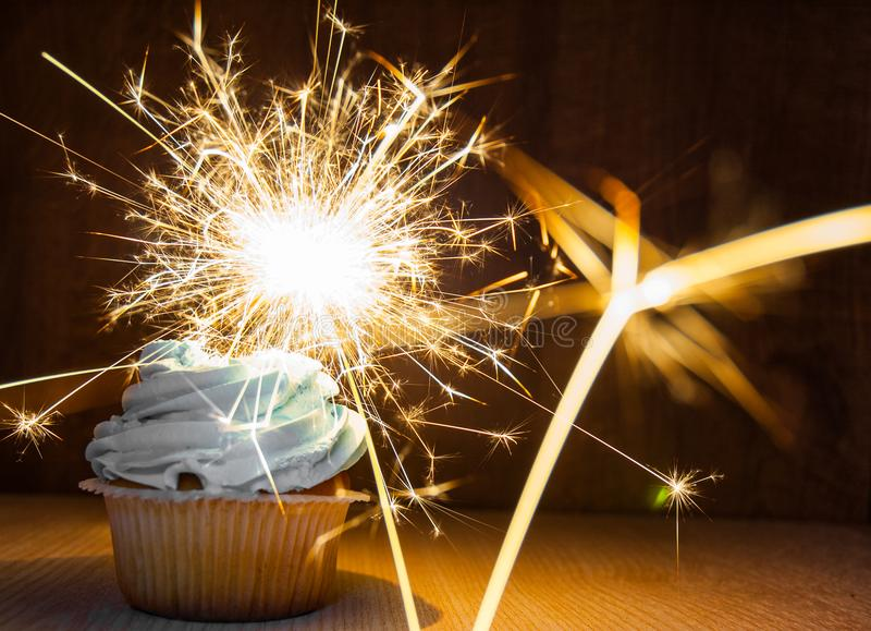 Cupcake with buttercream and sparkler on wooden table against dark background with copy space. stock photo