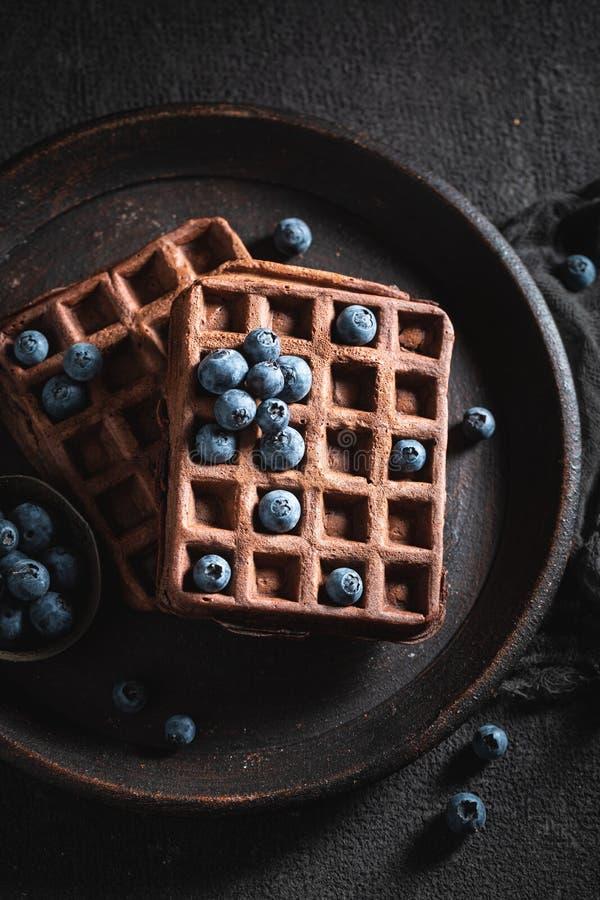 Yummy gofry z ciemną czekoladą i świeżymi czarnymi jagodami zdjęcia royalty free