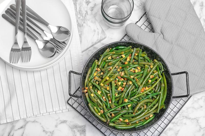 Yummy green beans with almonds in serving pan. On table stock images