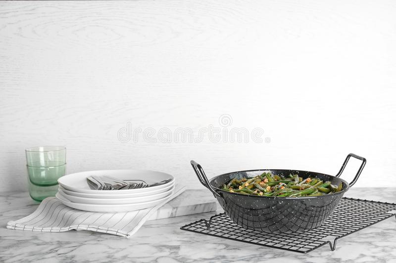 Yummy green beans with almonds in serving pan. On table royalty free stock photography