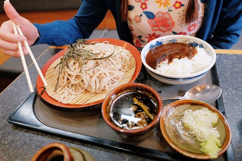 Yummy Japanse cusine, een vrouwelijke hand die eetstokjes, koude die sobanoedels en kerrierijst proberen te gebruiken op lijst wo royalty-vrije stock foto