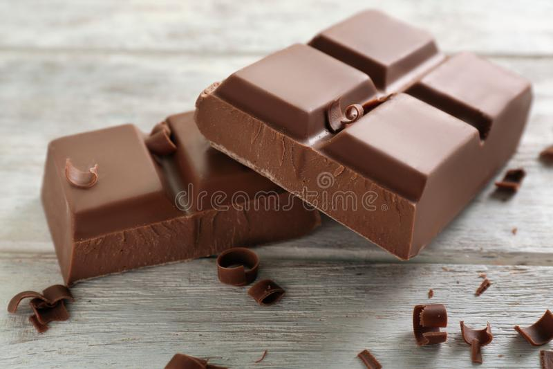 Yummy milk chocolate on wooden background stock photo