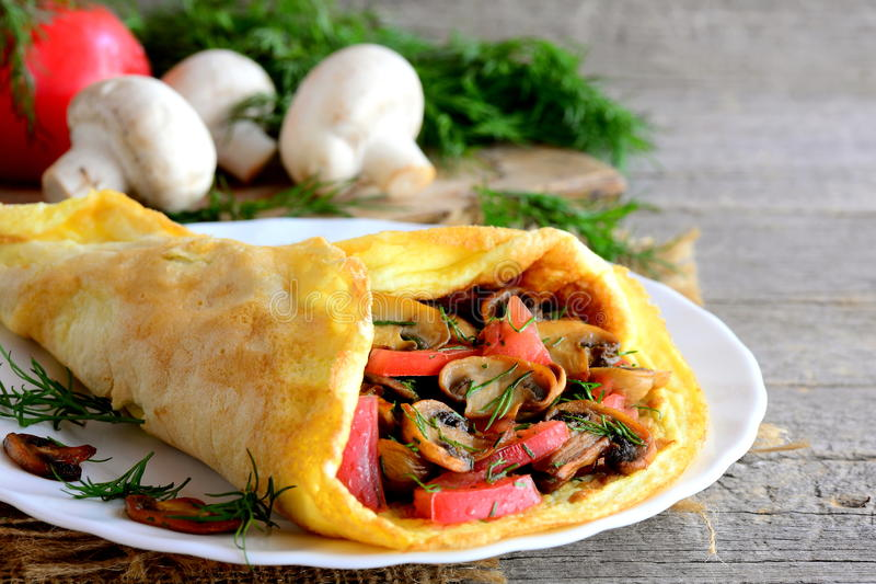 Yummy omlet z jarskim farszem Zdrowy omlet faszerujący z smażyć pieczarkami, świeżymi pomidorami i koperem na talerzu, zbliżenie zdjęcie stock