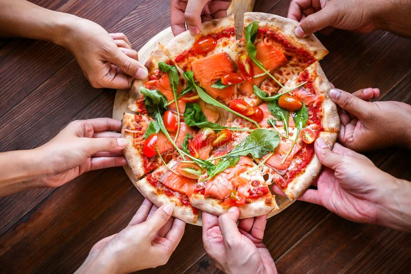 The customers or friend are taking it for eating delicious pizza. royalty free stock image