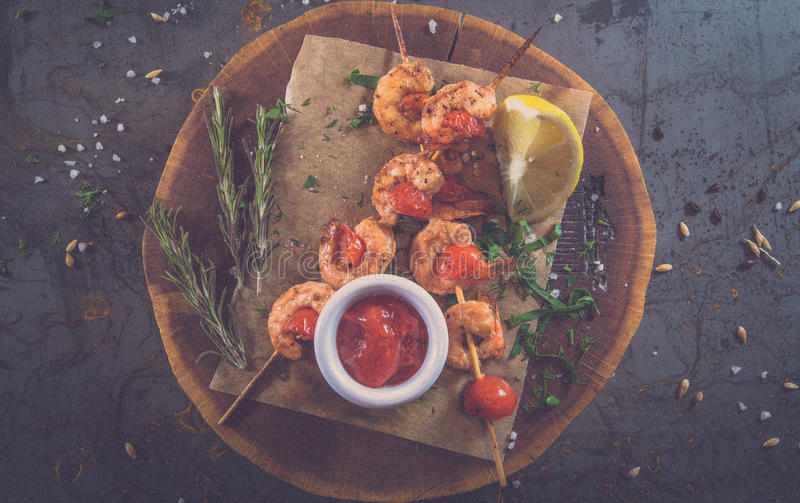 Yummy shrimp kebab on the wood plate and metall background royalty free stock photos