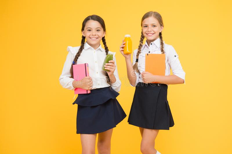 Yummy smoothie m Школьницы держа бутылку сока на желтой предпосылке Гасить жажду во время школы стоковое изображение rf