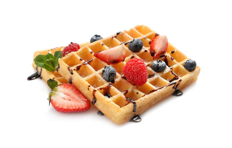 Yummy waffles with berries and chocolate syrup. On white background stock photography