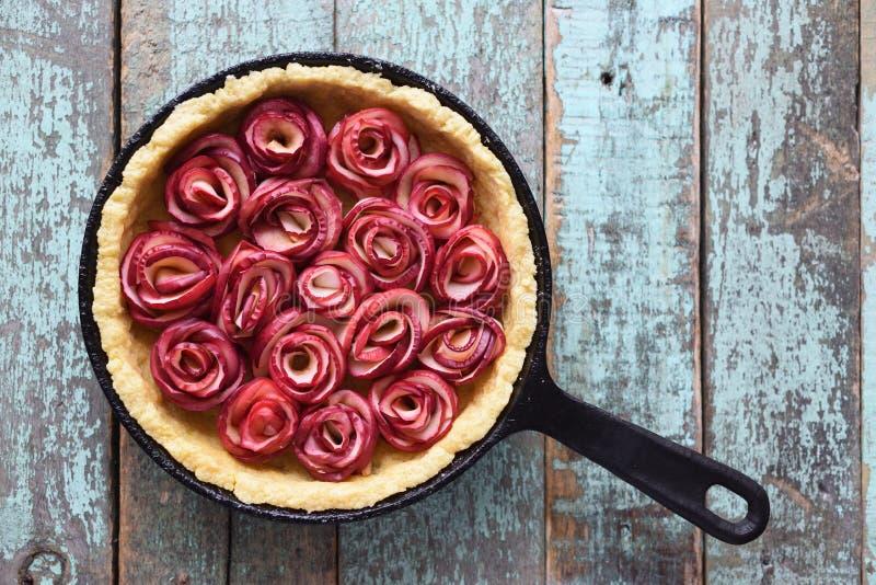Yummy zdrowy kulebiak Apple różany tarta w obsady żelaza niecce na starym błękicie fotografia royalty free