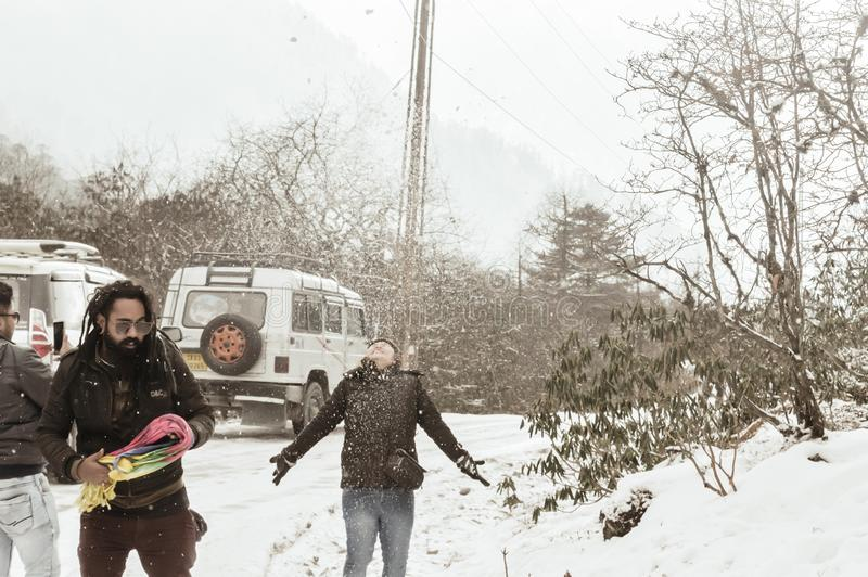 Yumthang Valley, Sikkim, India 1st January 2019: Group of Tourist in winter clothes enjoying snow at snowfall on a day with heavy royalty free stock photo