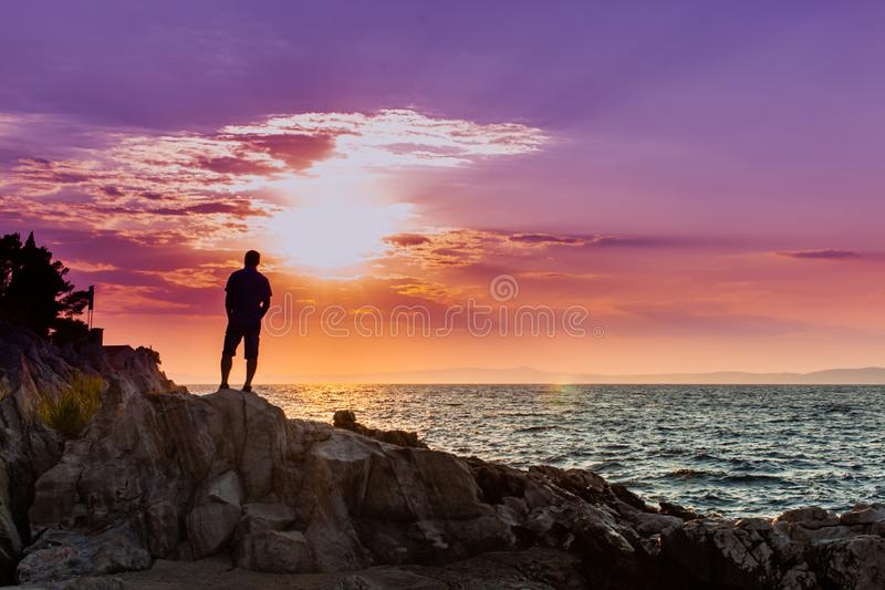 Yung man standing on a rock and looking at the sea sunset stock images