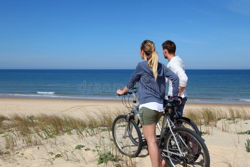 Yung par som cyklar på sandiga dyn arkivbild