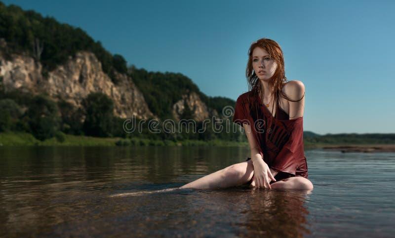 Yung rudzielec piękna dziewczyna w Burgundy koszulowym obsiadaniu w rzece fotografia stock
