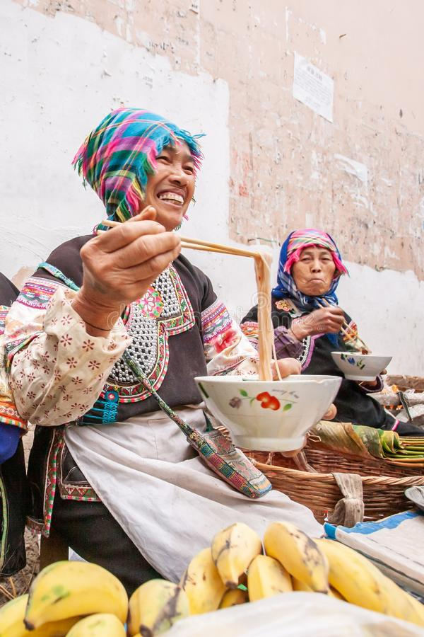 A group of chinese old women vendor wearing traditional costume eating noodle and laughing during sells fresh fruits and vegetable. Yunnan, China– MARCH 1 stock photography